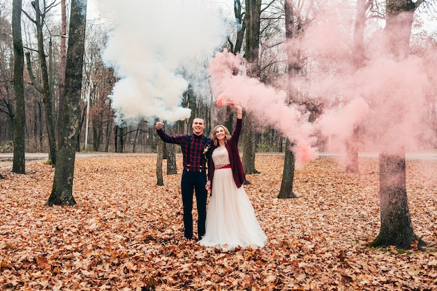 恋をしている若いカップルは、秋の小さな結婚式を祝い、発煙弾を楽しんでいます