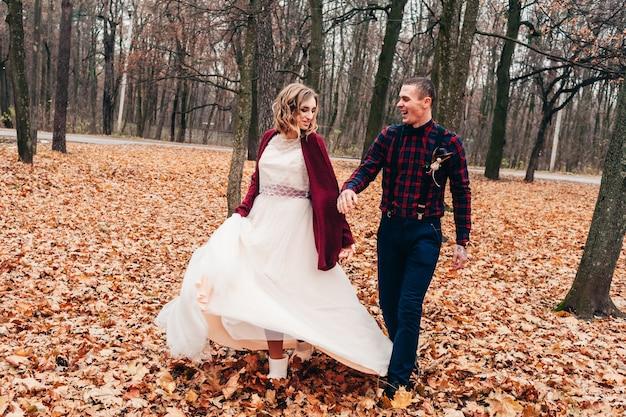 Молодая влюбленная пара празднует свою маленькую свадьбу осенью