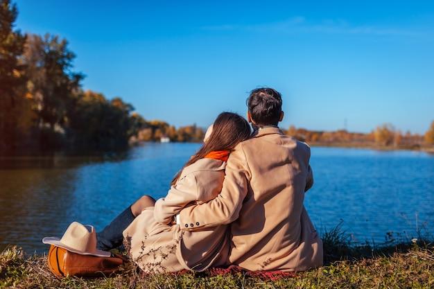 Молодая пара в любви, отдыхая у осеннего озера. счастливый мужчина и женщина, наслаждаясь природой и обниматься. отдых на природе