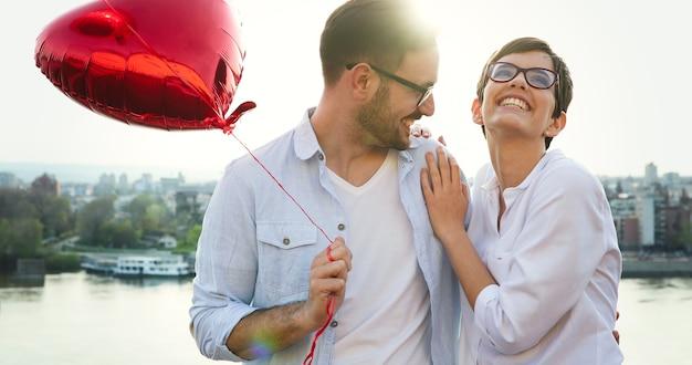 Молодая пара в любви, свидания и улыбка на открытом воздухе в день святого валентина