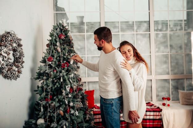 Молодая влюбленная пара украшает елку подготовка к новому году счастливая семья