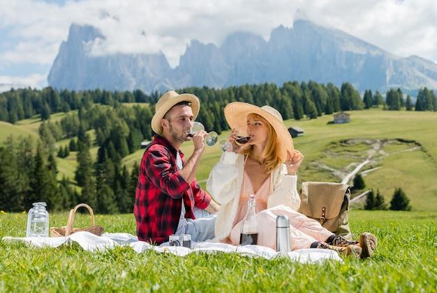 Молодая влюбленная пара делает пикник, посещая альпийские долины