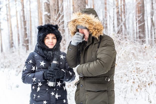 恋をしている若いカップルは魔法瓶から温かい飲み物を飲み、冬の自然を楽しんでいます。