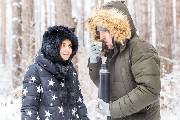 사랑에 빠진 젊은 부부는 보온병에서 뜨거운 음료를 마시고 겨울 자연을 즐긴다