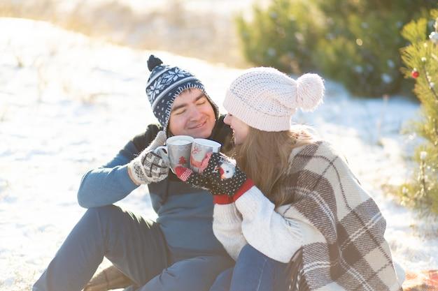 Молодая влюбленная пара пьет горячий напиток с зефиром, сидя зимой в лесу, заправляясь теплыми, удобными ковриками и наслаждаясь природой. они разговаривают и смеются за чашкой горячего напитка в лесу