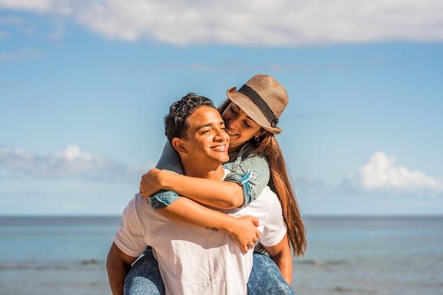 愛の若いカップルは幸せとレジャー活動を楽しんでいます-男性はピギーバックで女性を運び、喜びに満ちた笑顔-海の水と背景の青い空-夏休みの概念