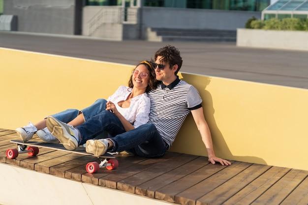 愛の若いカップルは、屋外で身も凍るようなロングボードのトレンディな男性と女性に抱き締めて日没の座をお楽しみください