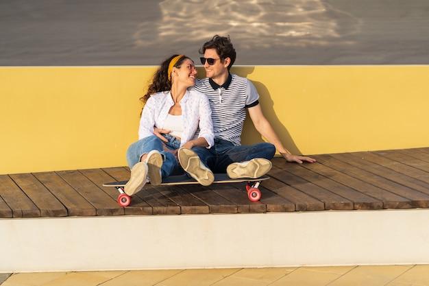 愛の若いカップルは、屋外で身も凍るようなロングボードのトレンディな男性と女性に抱き締めて日没の座をお楽しみください Premium写真