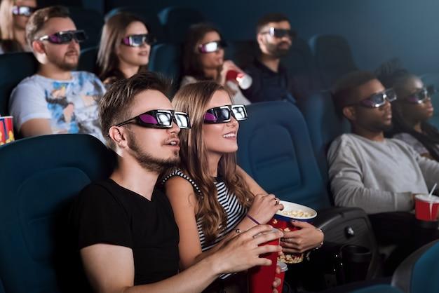 Молодая влюбленная пара вместе наслаждается 3d-фильмом во время свидания в кино