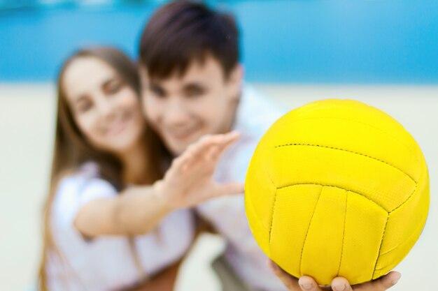 バレーボールで遊ぶ愛の女性の女の子と男性男性のティーンエイジャーの大人の若いカップル