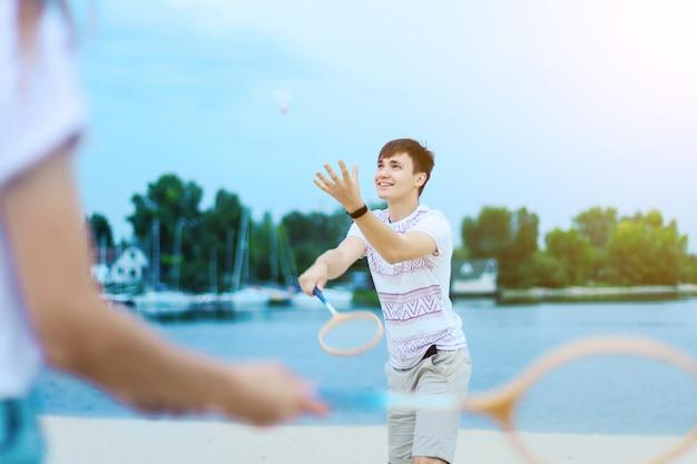 バドミントンで遊ぶ愛の女性の女の子と男性男性のティーンエイジャーの大人の若いカップル