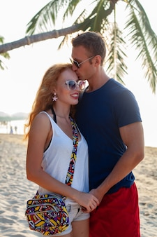 一緒に楽しんで夏のビーチで幸せな恋の若いカップル