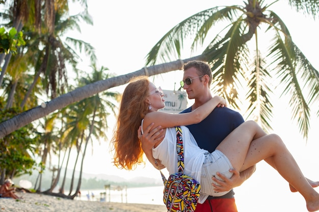 Молодая влюбленная пара счастлива на летнем пляже вместе весело