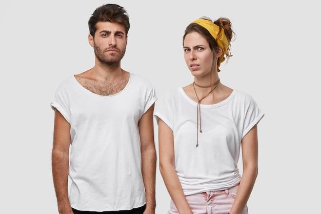 사랑에 빠진 젊은 부부는 표정을 불쾌하게하고 혐오감을 느끼며 일의 나쁜 결과에 불만족하며 흰색 티셔츠를 입고 노란색 머리띠를 착용합니다.