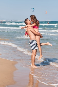 ビーチでロマンチックな優しい瞬間を持っている愛の若いカップル。