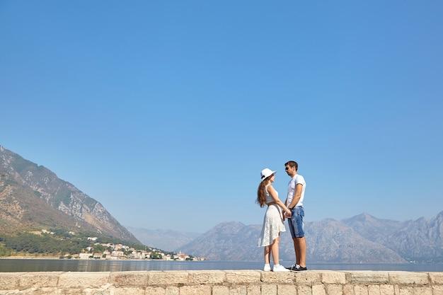 山の風景に対して手をつないで恋の若いカップル