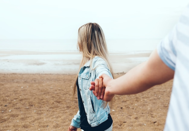 Молодая влюбленная пара, держась за руки, гуляет по пляжу на берегу моря в тумане