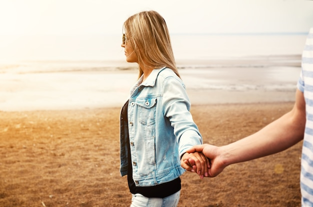 Молодая влюбленная пара, держась за руки, гуляет по пляжу на фоне летнего заката