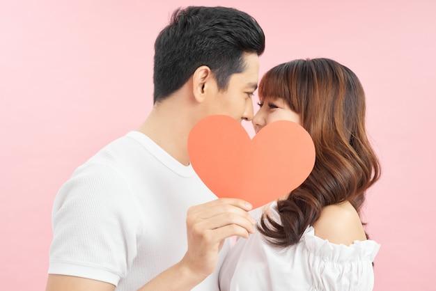 赤いハートを保持している愛の若いカップル