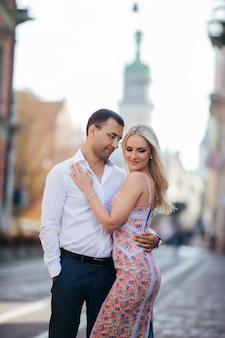 愛の若いカップルは市でお互いをハグします。
