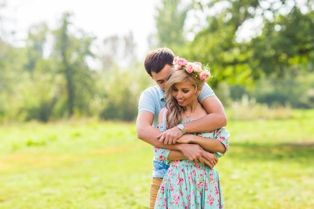 Молодая влюбленная пара обнимает друг друга на природе.