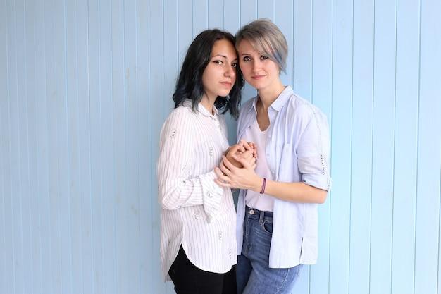 Молодая влюбленная пара обнимает друг друга на синем фоне