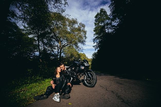 Молодая влюбленная пара обнимается и целуется возле черного спортивного мотоцикла на фоне лесной дороги