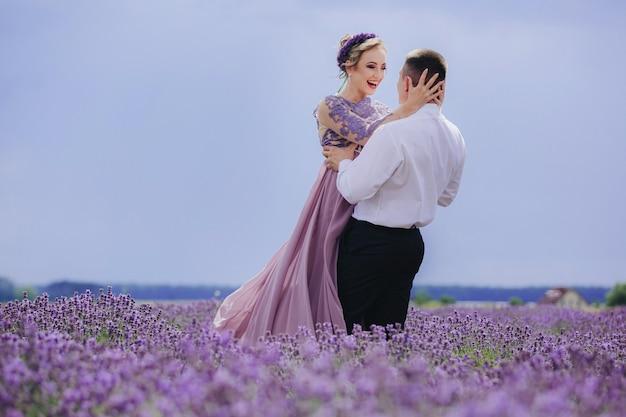 Молодая влюбленная пара обнимается и гуляет в лавандовом поле в летний пасмурный день