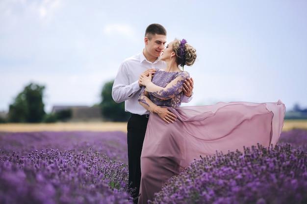 Молодая влюбленная пара обнимается и гуляет в лавандовом поле в летний день