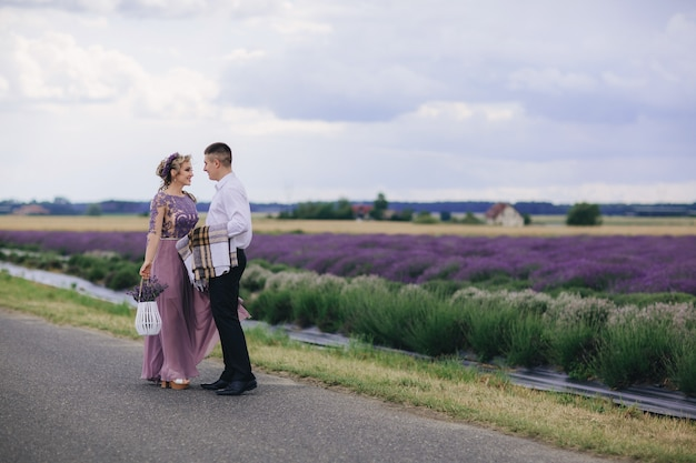 Молодая влюбленная пара обнимается возле лавандового поля в летний день