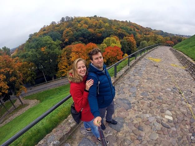 Молодая пара в любви обнимает и держится за руку. прогулка в осеннем лесу. красивый парк с сухими желтыми и красными листьями и разноцветными деревьями.