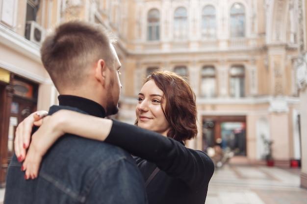 사랑에 빠진 젊은 부부는 도시 건축을 배경으로 도시에서 포옹하고 함께 시간을 보냅니다.