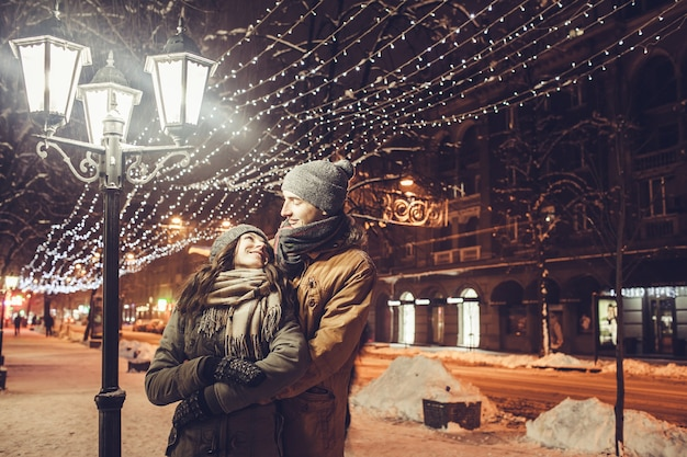 Молодая влюбленная пара обнимается под праздничным зимним освещением ночью