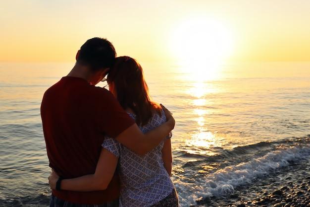 海岸で日没の抱擁で恋をしている若いカップル