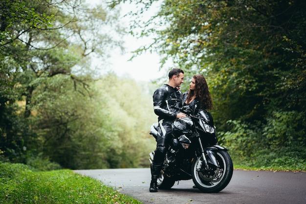 Молодая влюбленная пара в черной кожаной одежде возле черного спортивного мотоцикла на дороге