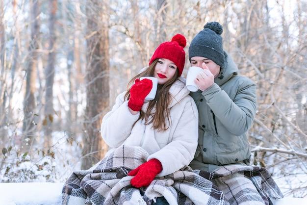 Молодая влюбленная пара в зимнем парке пьет чай и укутывается в одеяло. фотосессия love story.