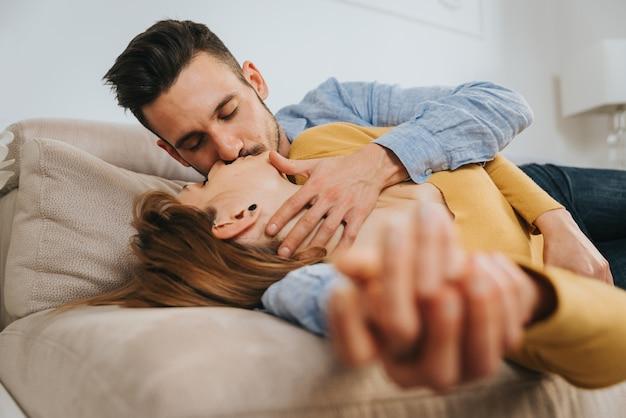 Молодая пара в любви, целуя взявшись за руки дома на диване.
