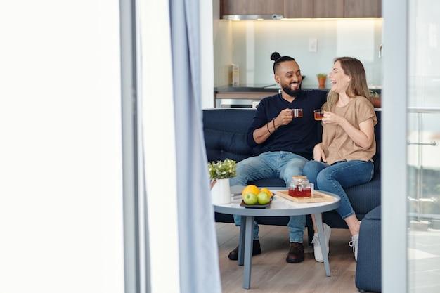 家でクッキーとお茶を飲むときに笑ったり冗談を言ったりするのが大好きな若いカップル