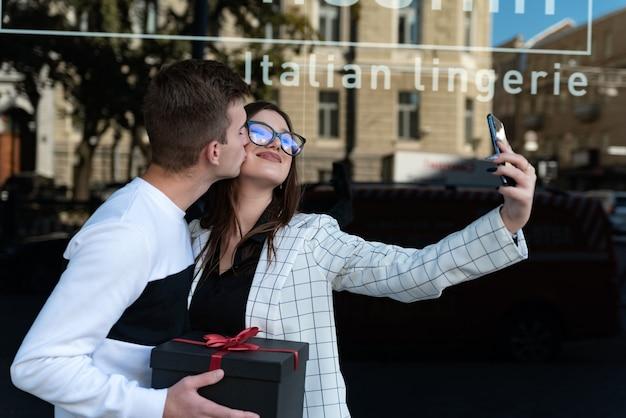 사랑에 빠진 젊은 부부는 손에 선물을 들고 셀카를 만듭니다. 남자는 여자 친구에게 선물을 주고 키스를 합니다. 사랑에 웃는 커플.