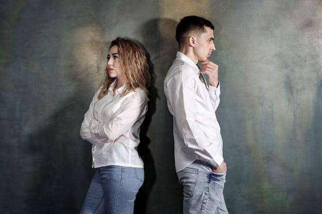 Молодая влюбленная пара мужчина и женщина обижены друг на друга и никто не хочет мириться, они стоят спиной к стене, подтянутые