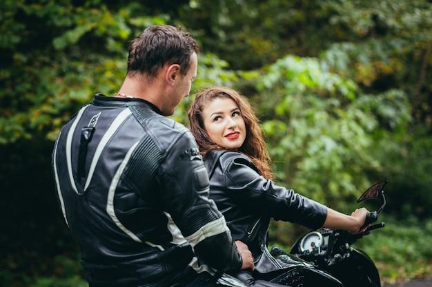 Молодая влюбленная пара на мотоцикле по дороге в лес