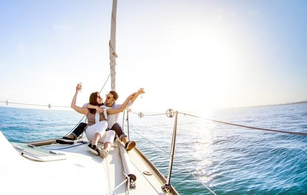 Молодая влюбленная пара на парусной лодке с шампанским на закате