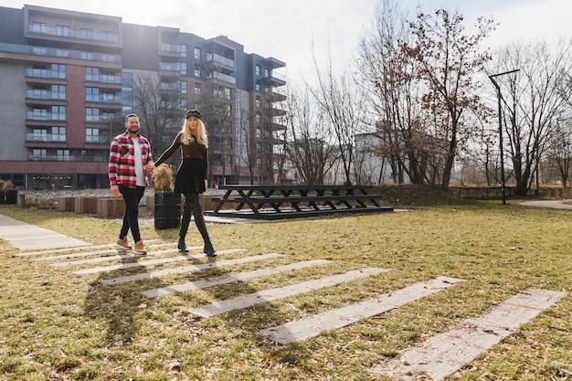 屋外で恋をしている若いカップル。週末の休暇で春の旧市街を歩いている若い流行に敏感な人々のかわいいカップル。幸せな男と女。トラベル。