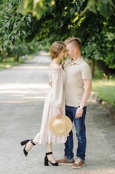 屋外の愛の若いカップル。フィールドでポーズをとって夏にスタイリッシュなファッションの若いカップルの見事な官能的な屋外のポートレート
