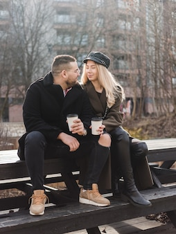 Молодая пара в любви на открытом воздухе. путешественники с чашками кофе гуляют по весеннему парку. прекрасный солнечный день. молодая пара пьет кофе с собой