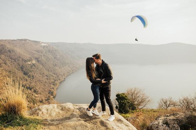 야외에서 포용하고 호수와 산 배경에서 함께 웃고 사랑에 젊은 부부