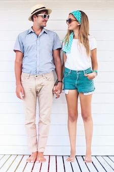 Молодая влюбленная пара позирует возле кафе на белом пляже в летних ретро ярких нарядах, держась за руки