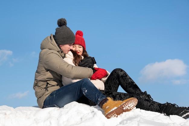 愛の若いカップルは雪の上に座って抱きしめます。背景の青い空。