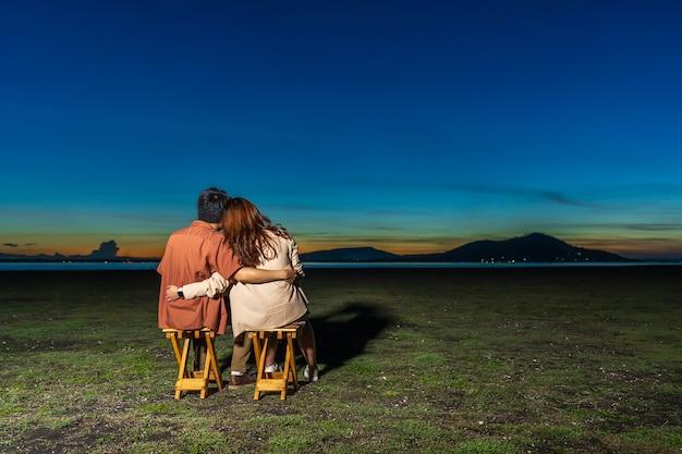 夜に提出された草に座って抱き締めるのが大好きな若いカップル