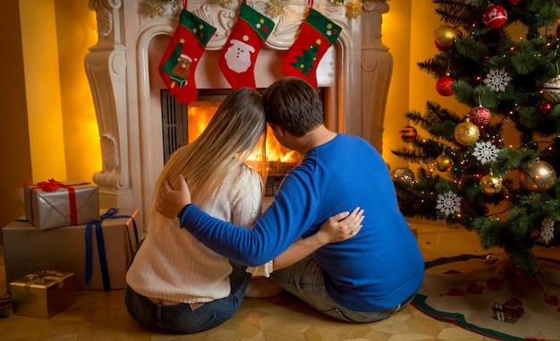 Молодая влюбленная пара сидит у камина, украшенного или рождественского, и смотрит на огонь